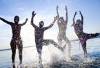 gente saltando en la playa beneficios del agua de mar